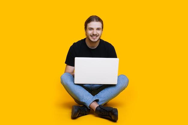 Kaukasischer unrasierter mann mit langen haaren, die mit gekreuzten beinen sitzen und etwas am computer tippen, während sie auf einem gelben hintergrund aufwerfen