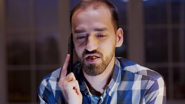 Kaukasischer unternehmer, der ein geschäftsgespräch auf dem handy führt. geschäftsmann, der während der nächtlichen arbeitszeit im home office arbeitet.