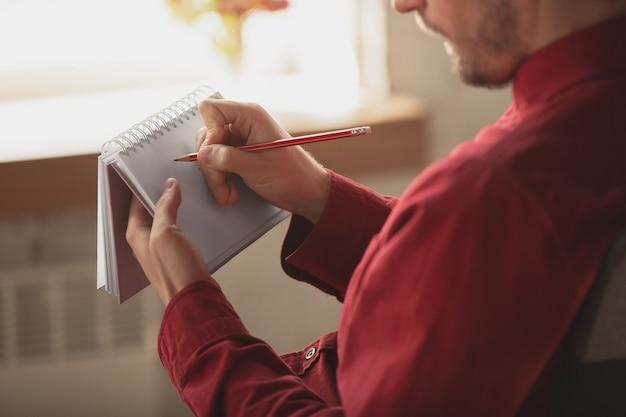 Kaukasischer unternehmer, geschäftsmann, manager, der im büro arbeitet, nahaufnahme. notizen machen, bericht schreiben oder aufgaben erledigen. konzept von arbeit, finanzen, geschäft, erfolg und führung. frist, beeilen sie sich.