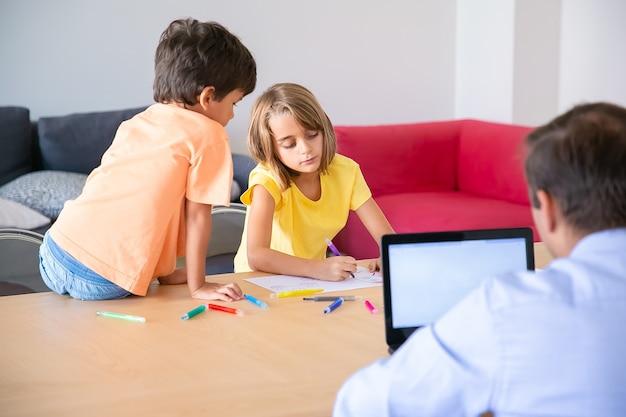 Kaukasischer vater, der an laptop und niedlichen kindern arbeitet, die kritzeleien am tisch malen. konzentrierte blonde mädchenzeichnung mit marker und bruder, die sie betrachten. kindheit, kreativität und wochenendkonzept