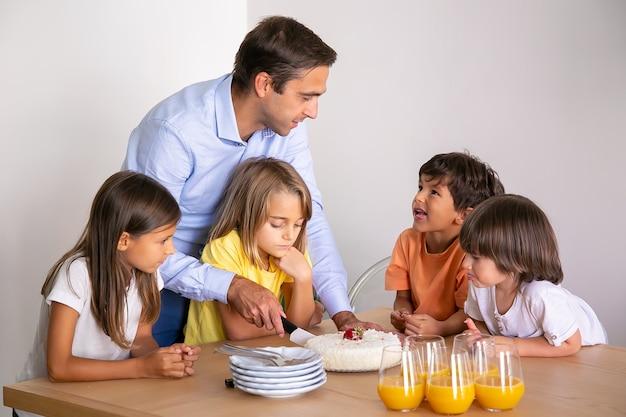 Kaukasischer vater, der köstlichen kuchen für kinder schneidet. nette kleine kinder, die tisch umgeben, geburtstag zusammen feiern, reden und auf nachtisch warten. kindheits-, feier- und feiertagskonzept