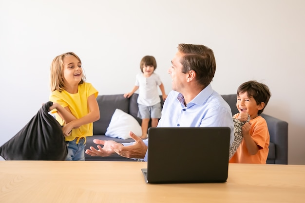 Kaukasischer vater, der mit verspielten kindern spricht und am tisch sitzt. glücklicher vater mittleren alters, der laptop-computer verwendet, wenn kinder zu hause mit kissen spielen. konzept für kindheit und digitale technologie