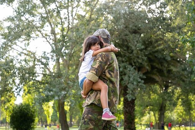 Kaukasischer vater in der armeeuniform, die tochter umarmt. vater mittleren alters, der im stadtpark steht. nettes mädchen, das auf seinen händen sitzt und papa am hals umarmt. kindheits-, wochenend- und militärelternkonzept