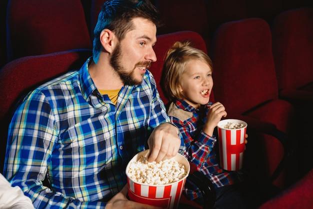 Kaukasischer vater und sohn schauen sich einen film in einem kino, haus oder kino an.