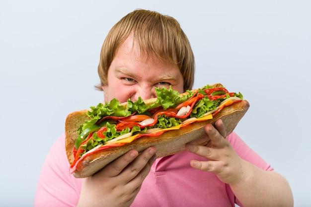 Kaukasischer verrückter blonder dicker mann, der ein riesiges sandwich hält