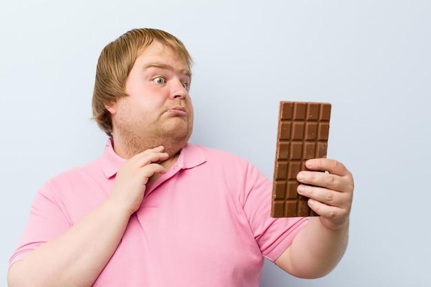 Kaukasischer verrückter blonder dicker mann, der eine schokoladentablette hält