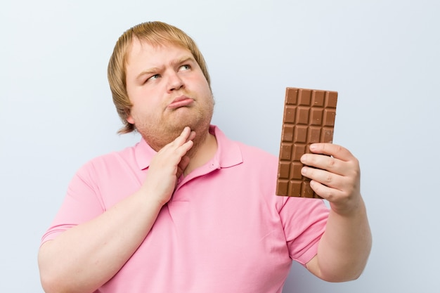 Kaukasischer verrückter blonder dicker mann, der eine schokoladentafel hält