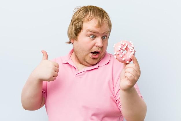 Kaukasischer verrückter blonder dicker mann, der einen donuts hält