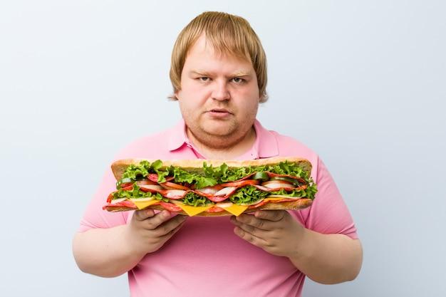 Kaukasischer verrückter blonder fetter mann, der ein riesiges sandwich hält