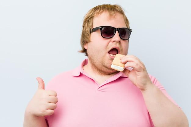 Kaukasischer verrückter blonder fetter mann, der eine eiscreme hält