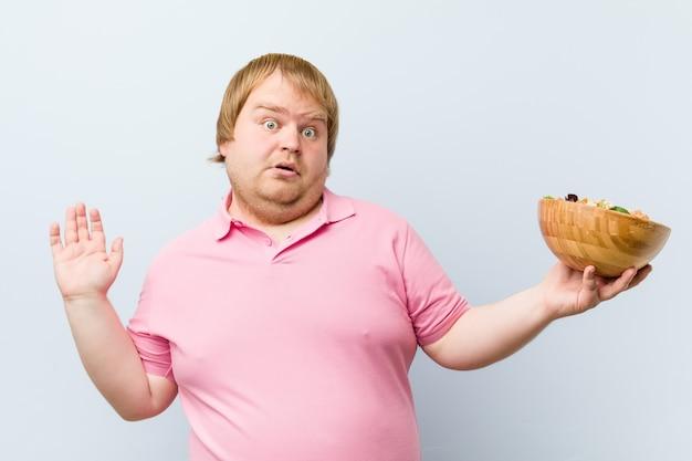 Kaukasischer verrückter blonder fetter mann, der eine salatschüssel hält