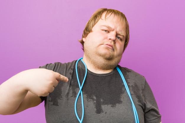 Kaukasischer verrückter blonder fetter mann, der mit einem seilspringen schwitzt