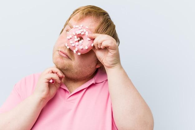Kaukasischer verrückter blonder fetter mann, halten schaumgummiringe