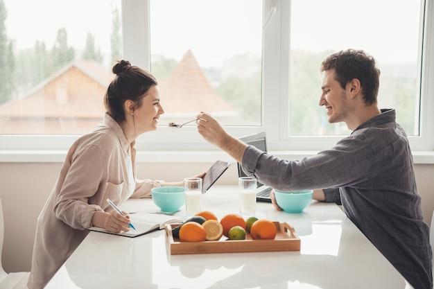 Kaukasischer vorsichtiger mann füttert seine freundin, während er zusammen in der küche am laptop arbeitet