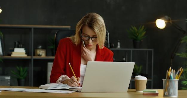 Kaukasischer weiblicher büroangestellter, der am tisch sitzt und auf handy spricht, während er am laptop arbeitet.