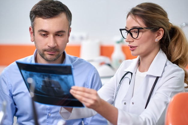 Kaukasischer weiblicher zahnarzt, der röntgenstrahl erklärt