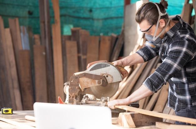 Kaukasischer zimmermann, der holz mit kreissäge schneidet, die neue möbel schafft