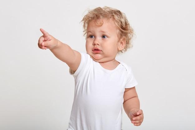 Kaukasisches baby, das mit zeigefinger weg zeigt, sieht etwas interessantes, tragendes t-shirt
