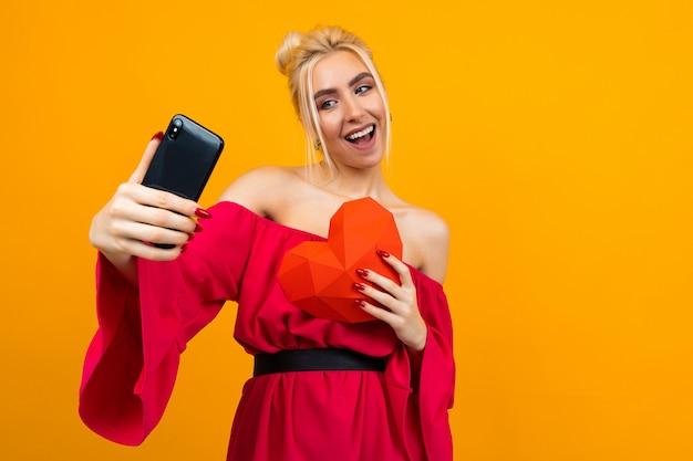 Kaukasisches blondes mädchen in einem roten kleid macht selfie am telefon mit einem roten herzen aus papier auf einem orangefarbenen studiohintergrund
