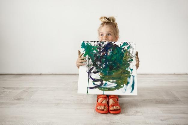 Kaukasisches blondes vorschulmädchen, das bild zeigt, das sie malte. entzückendes kind, das leinwand hält. glückliches kindheitskonzept.