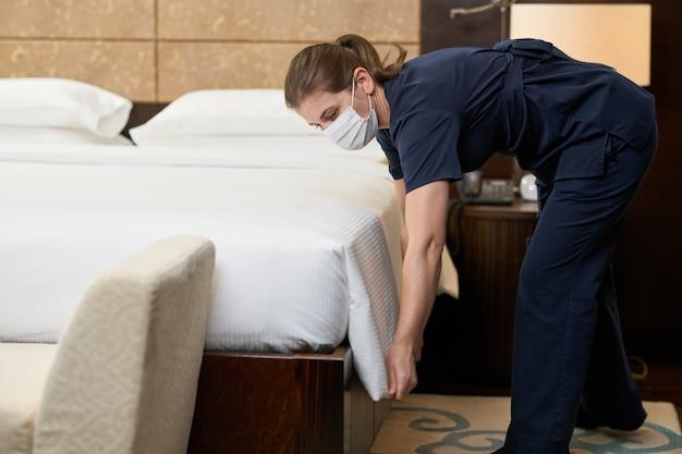 Kaukasisches dienstmädchen mit maske und reinigungsbett im luxushotelzimmer hotelservice-konzept