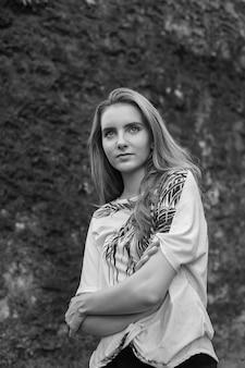 Kaukasisches dünnes natürliches attraktives weibliches modell steht vor steinmauer