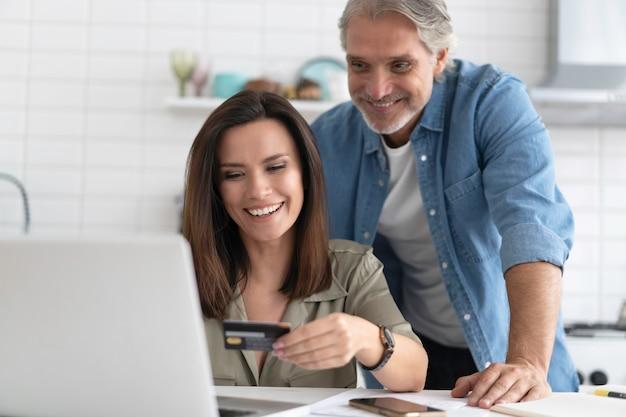 Kaukasisches ehepaar, das am online-shopping beteiligt ist und zahlungsinformationen von der kreditkarte in der mobilen anwendung eingibt