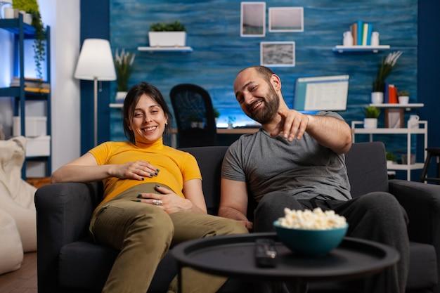 Kaukasisches ehepaar erwartet kind beim entspannen zu hause. junge schwangere frau, die mit der hand auf dem babybauch lächelt, während der mann auf das fernsehen zeigt, in die kamera schaut und fernsieht