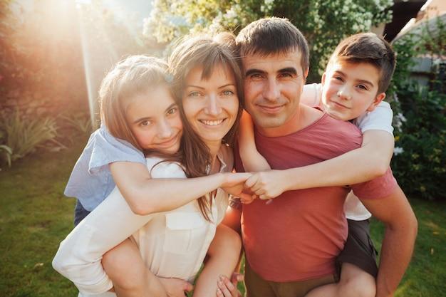 Kaukasisches elternteil, das ihre kinder im park trägt