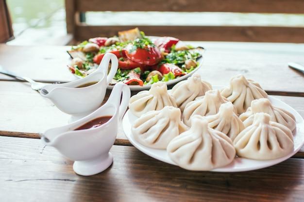 Kaukasisches essen kinkali auf einem teller auf einem holztisch in einem café