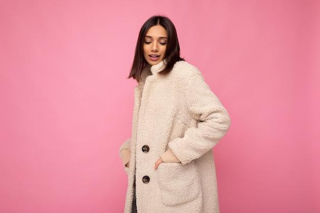 Kaukasisches foto einer attraktiven, selbstbewussten, stilvollen jungen brünetten, die einen warmen, warmen mantel im herbst trägt, einzeln auf rosafarbenem hintergrund mit leerem raum. modekonzept
