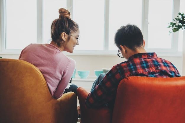 Kaukasisches geschäftspaar, das von zu hause aus am laptop im sessel arbeitet, während brillen unter verwendung des laptops tragen