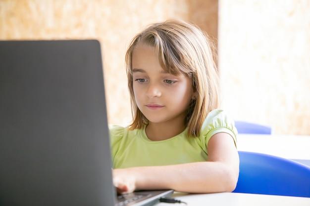 Kaukasisches hübsches mädchen, das auf laptop-computer tippt