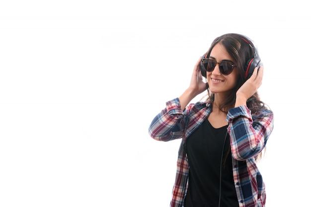 Kaukasisches junges mädchen, das musik mit den großen kopfhörern lokalisiert auf weißem hintergrund hört