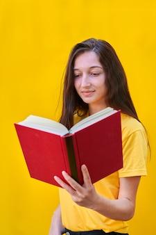 Kaukasisches junges mädchen mit langen brünetten haaren, die ein rotes buch lesen