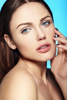 Kaukasisches junges modell mit nacktem make-up, das ihre perfekte saubere haut auf blau berührt