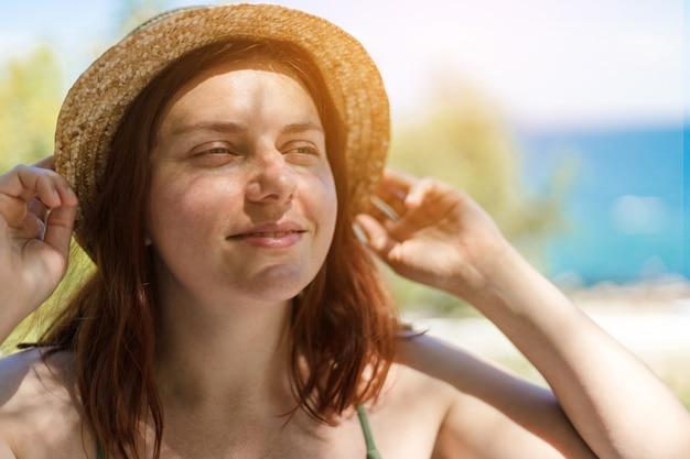 Kaukasisches junges schönes rothaariges mädchen in einem strohhut lächelnd, einen urlaub am meer genießt.