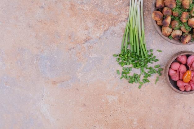 Kaukasisches khinkali in einer holzschale mit kräutern und mariniertem gemüse.