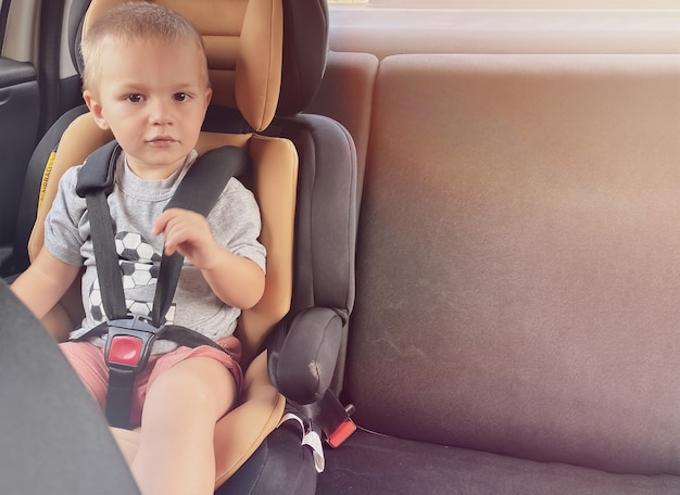 Kaukasisches kind auf einem schwarzen autositz mit pfirsichmitte. autosicherheitskonzept, autovermietung mit kind.