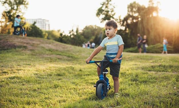 Kaukasisches kind, das das fahrrad in einem grünen feld voll gras während eines sommersonnenuntergangs reitet