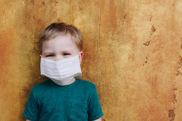 Kaukasisches kind, das medizinische schutzmaske auf seinem gesicht während der globalen coronavirus-covid-19-virus-pandemie trägt