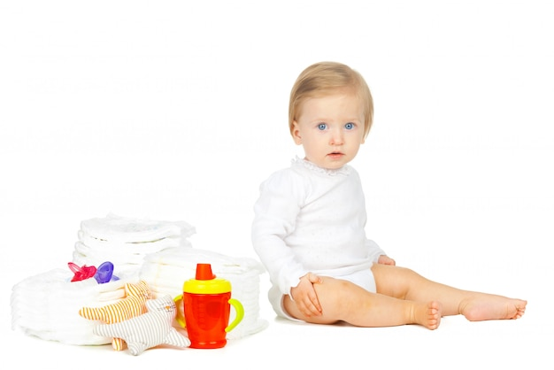 Kaukasisches kind mit den gestapelten windeln und spielwaren lokalisiert auf weiß