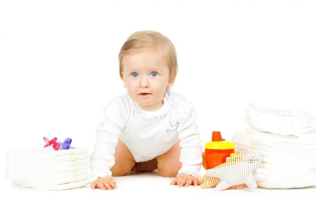 Kaukasisches kind mit den gestapelten windeln und spielwaren lokalisiert auf weißem hintergrund