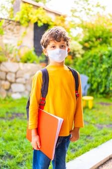 Kaukasisches kind mit gesichtsmaske bereit für den schulanfang. neue normalität, soziale distanz, coronavirus-pandemie, covid-19. orange t-shirt, rucksack und notizblock in der hand