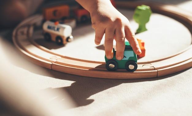 Kaukasisches kind spielt mit spielzeugeisenbahn auf der eisenbahn auf dem boden