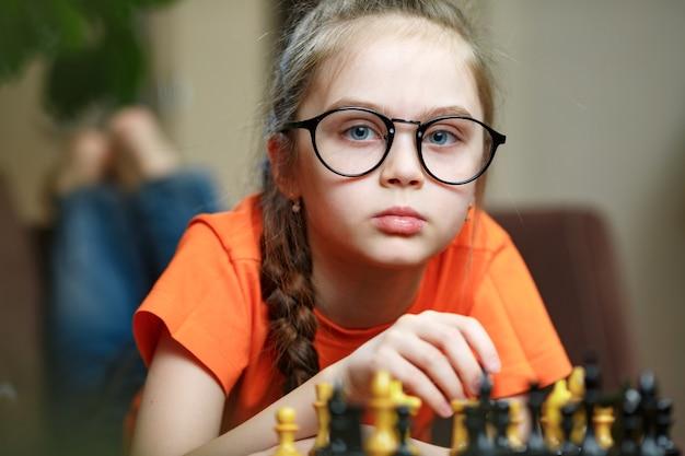 Kaukasisches kleines mädchen in den gläsern, die ein schachspiel denken, das zu hause während der quarantäne schach spielt. die frühkindliche entwicklung.