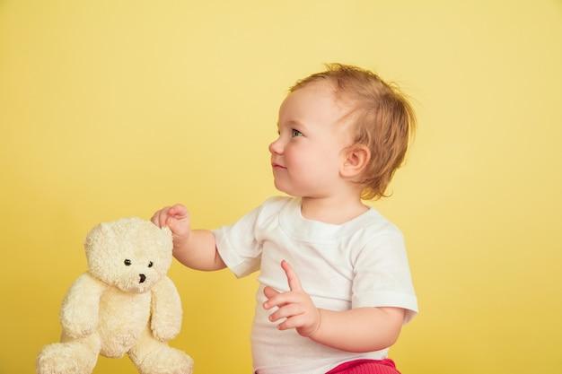 Kaukasisches kleines mädchen, kinder lokalisiert auf gelbem studiohintergrund. porträt des niedlichen und entzückenden kindes, baby, das mit teddybär spielt. konzept von kindheit, familie, glück, neuem leben, bildung.