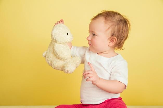 Kaukasisches kleines mädchen, kinder lokalisiert auf gelbem studiohintergrund. porträt des niedlichen und entzückenden kindes, baby, das mit teddybär spielt.