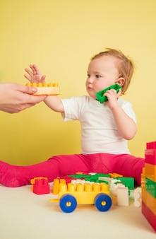 Kaukasisches kleines mädchen, kinder lokalisiert auf gelbem studiohintergrund. porträt des niedlichen und entzückenden kindes, baby spielend und sieht ernst aus.