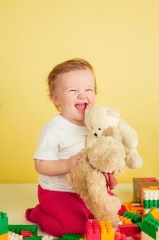 Kaukasisches kleines mädchen, kinder lokalisiert auf gelbem studiohintergrund. porträt des niedlichen und entzückenden kindes, des babys, das spielt und lacht.